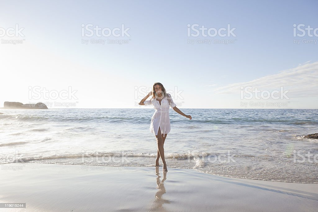 Woman walking in surf on beach stock photo