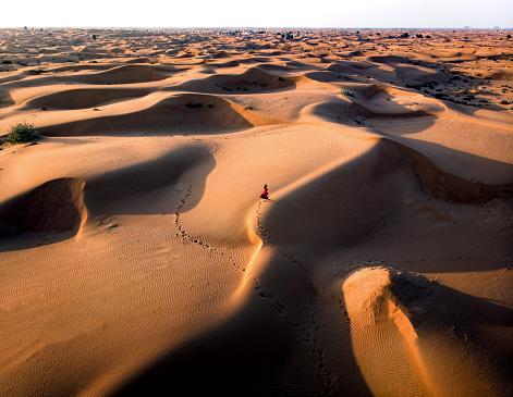 Woman walking in the desert aerial view