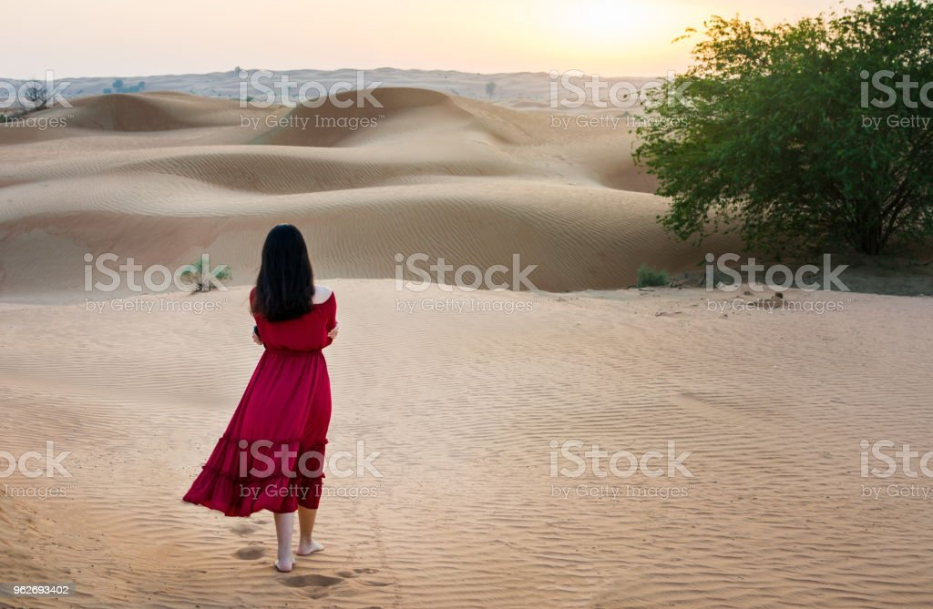 Woman walking in the desert at sunset stock photo