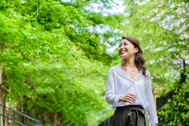 woman walking in the fresh green - forest bathing foto e immagini stock