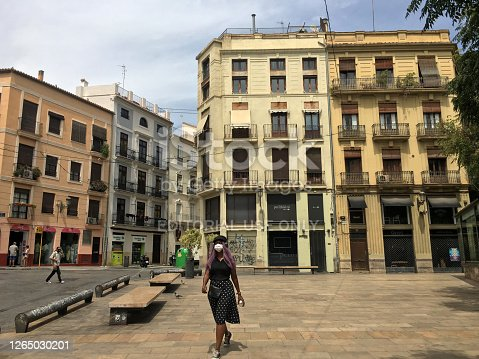 Valencia, Spain - August 10, 2020: Woman wearing protective face mask walking in the old part of the city. After the confinement, the use of masks is mandatory in public areas