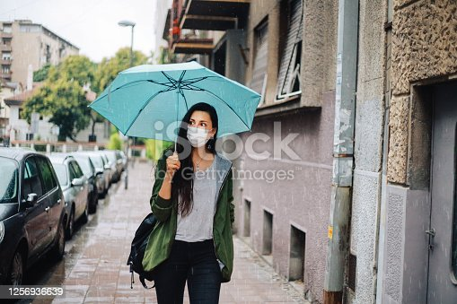 Young woman getting caught in the rain while walking in the city centre, wearing a protective face mask during the coronavirus pandemic.
