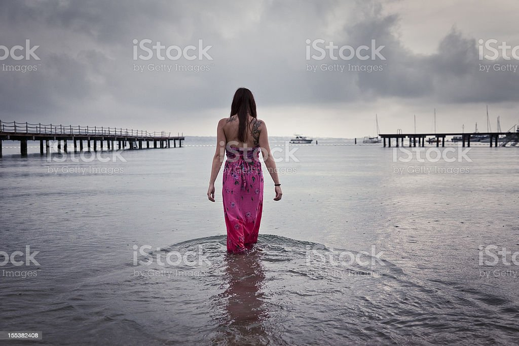 Woman walking in the sea on rainy day stock photo