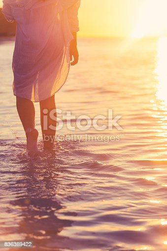 istock Woman walking in the water alone on the beach. 836369422