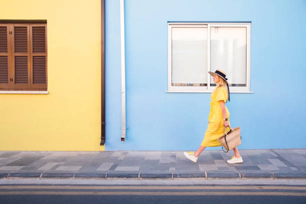 Woman walking in yellow dress at Paphos old city stock photo