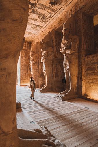 Young Caucasian woman walking inside  Abu Simbel temples