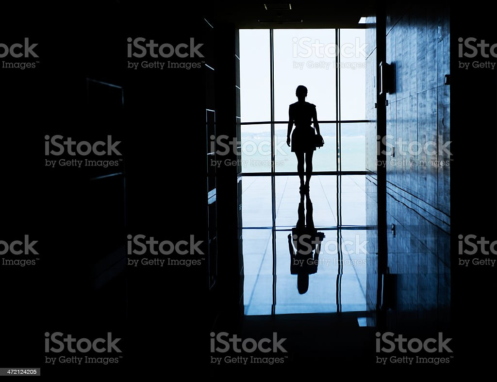 A woman walking into the light down a dark hallway stock photo