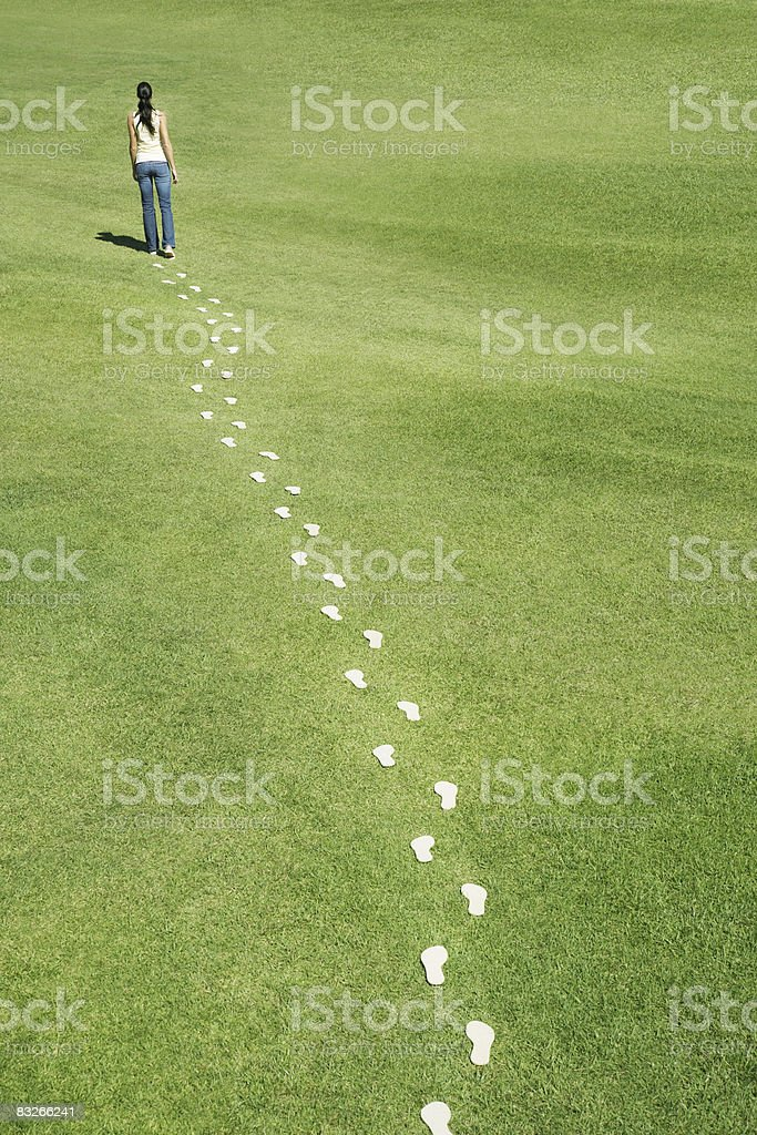 Woman walking leaving trail of footprints royalty-free stock photo