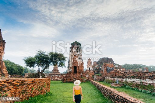 Young Caucasian woman walking near the ruins of ancient Buddhist Temple, Ayutthaya, Thailand