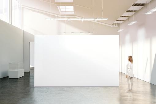 Woman walking near blank white wall mockup in modern gallery