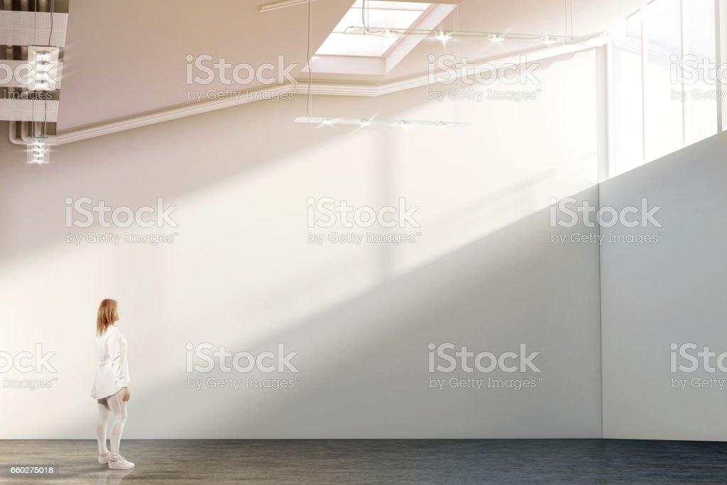 Woman walking near blank white wall mockup in modern gallery stock photo