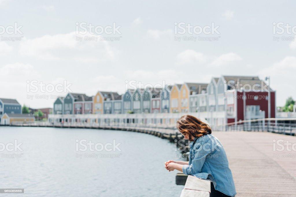Woman walking near colorful buildings near the lake zbiór zdjęć royalty-free