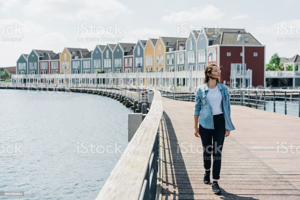 Woman walking near colorful buildings near the lake royalty-free stock photo