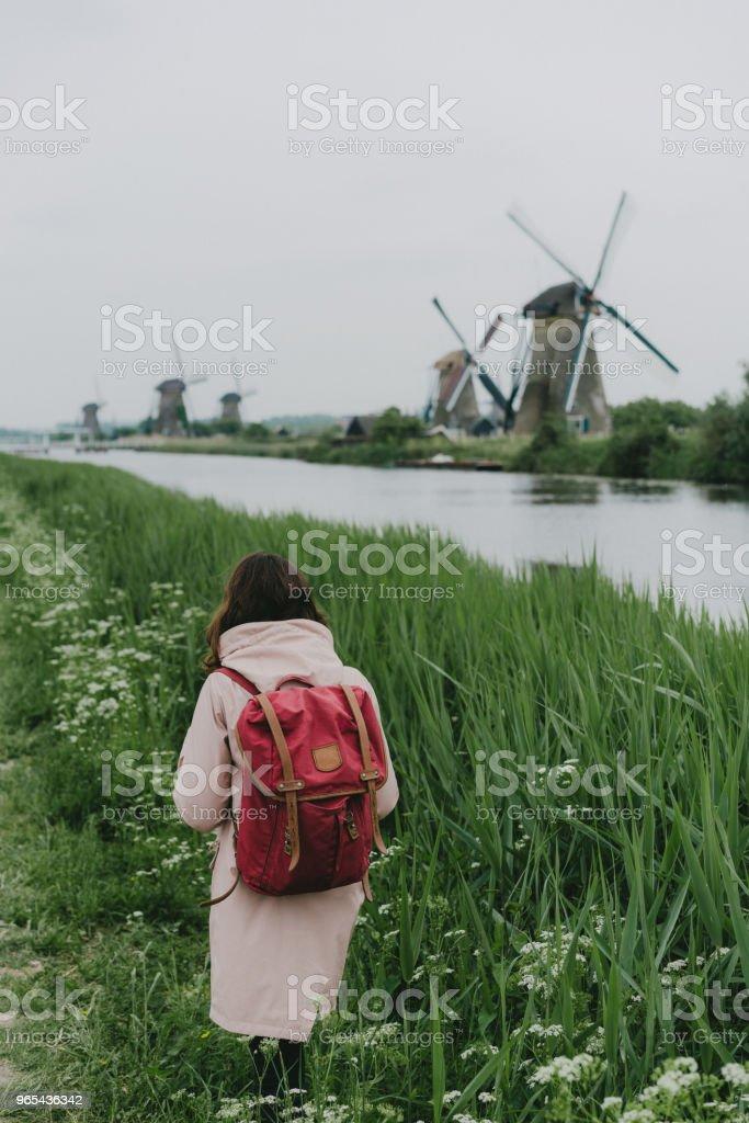 Femme qui marche près de moulins à vent aux Pays-Bas - Photo de Admirer le paysage libre de droits
