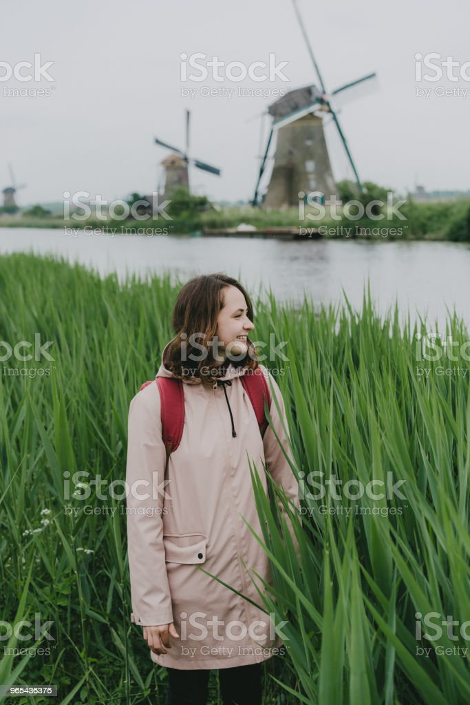 Woman walking near windmills in the Netherlands zbiór zdjęć royalty-free