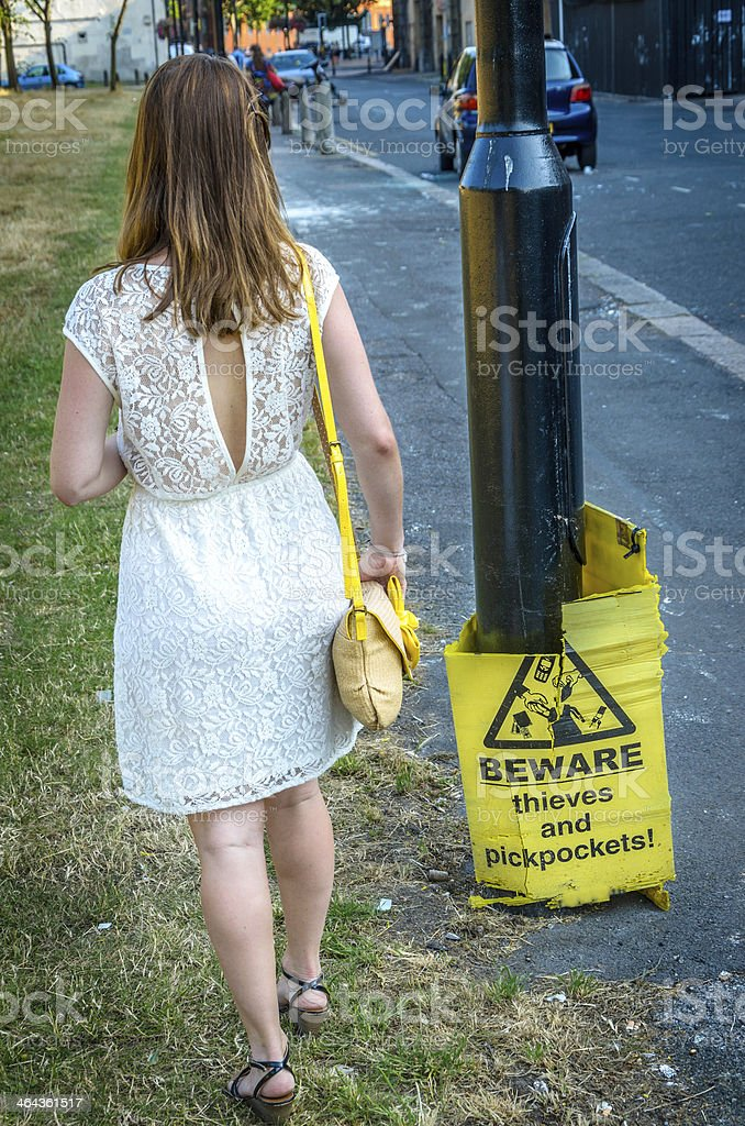 Woman walking next to a warning sign royalty-free stock photo
