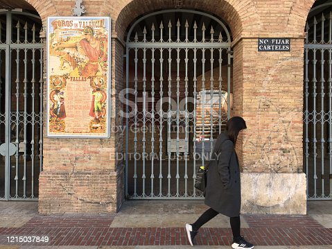 Valencia, Spain - February 26, 2020: Woman passing by the entrance doors of the bullfight ring in the city downtown. It was built between 1850 and 1859 in the neoclassical style, inspired by civil Roman architecture such as the Colosseum in Rome or the Arena of Nîmes in France