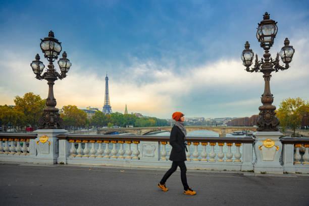 Woman walking on a bridge in Paris stock photo