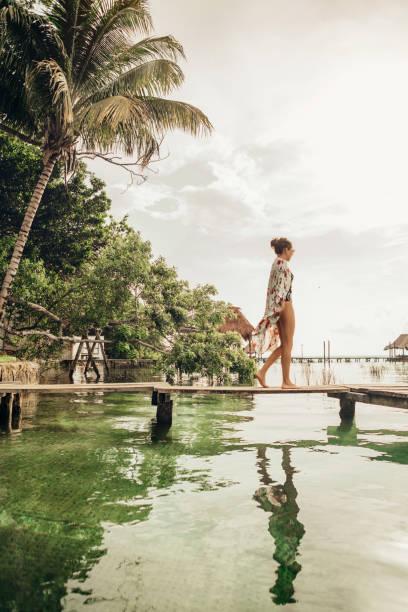 frau zu fuß auf einem pier an einer lagune - mexikanische möbel stock-fotos und bilder