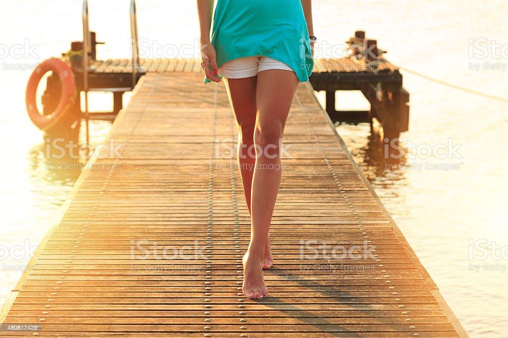 Woman walking on a quay stock photo