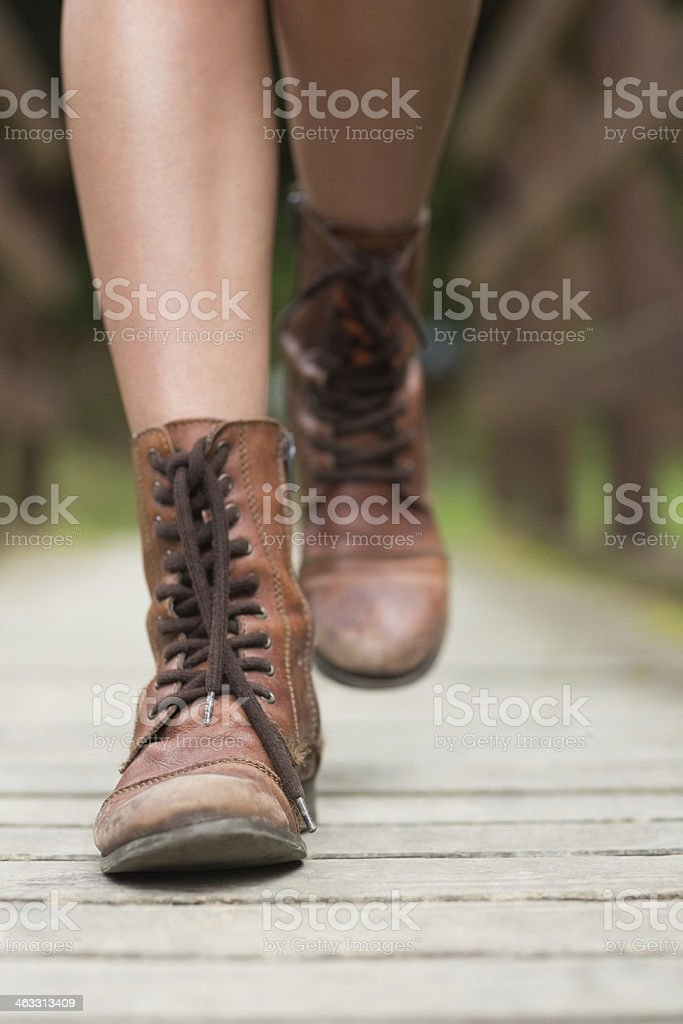 Woman walking on a wooden bridge stock photo