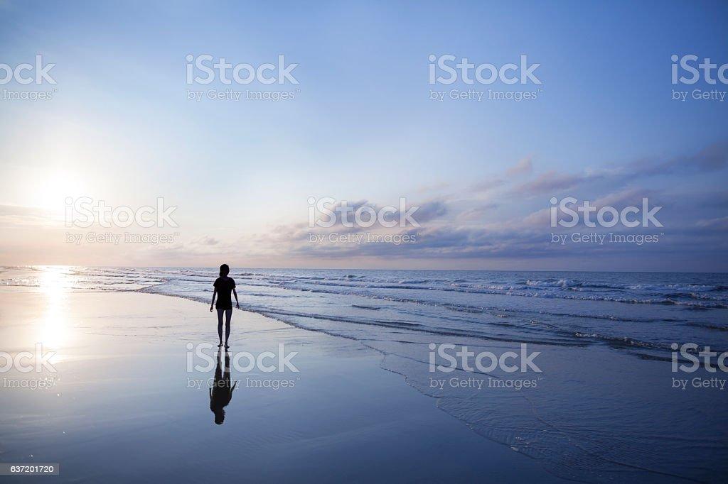 Mujer caminando en la playa al atardecer - foto de stock
