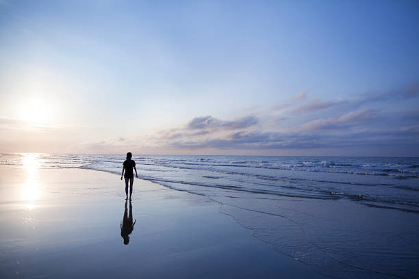 Woman walking on beach at sunrise stock photo