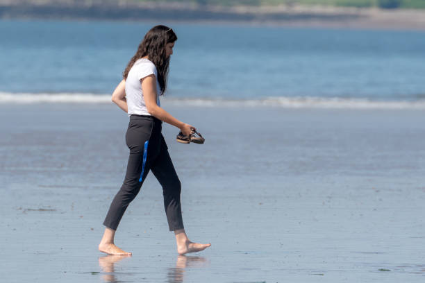 Woman Walking On Beach Saint John, NB, Canada - July 20, 2019: A woman walks barefoot across a wet public beach at low tide on a sunny day. She is dressed in a white tee shirt and black pants, and is carrying her sandals. wet clothing women t shirt stock pictures, royalty-free photos & images