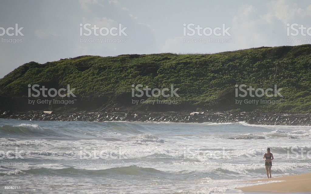 Woman walking on beach with cliff background royalty-free stock photo