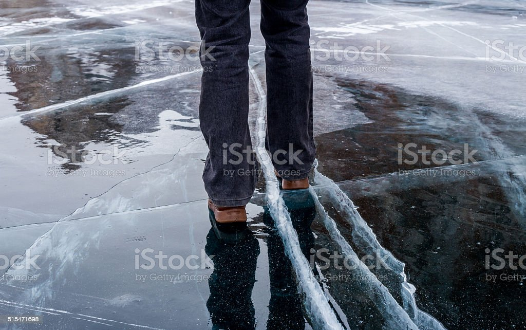 Woman walking on blue cracked ice of frozen lake Baikal stock photo