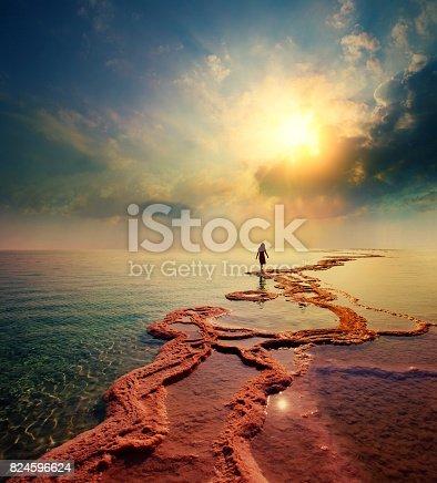 istock Woman walking on Dead Sea salt shore towards the sun 824596624