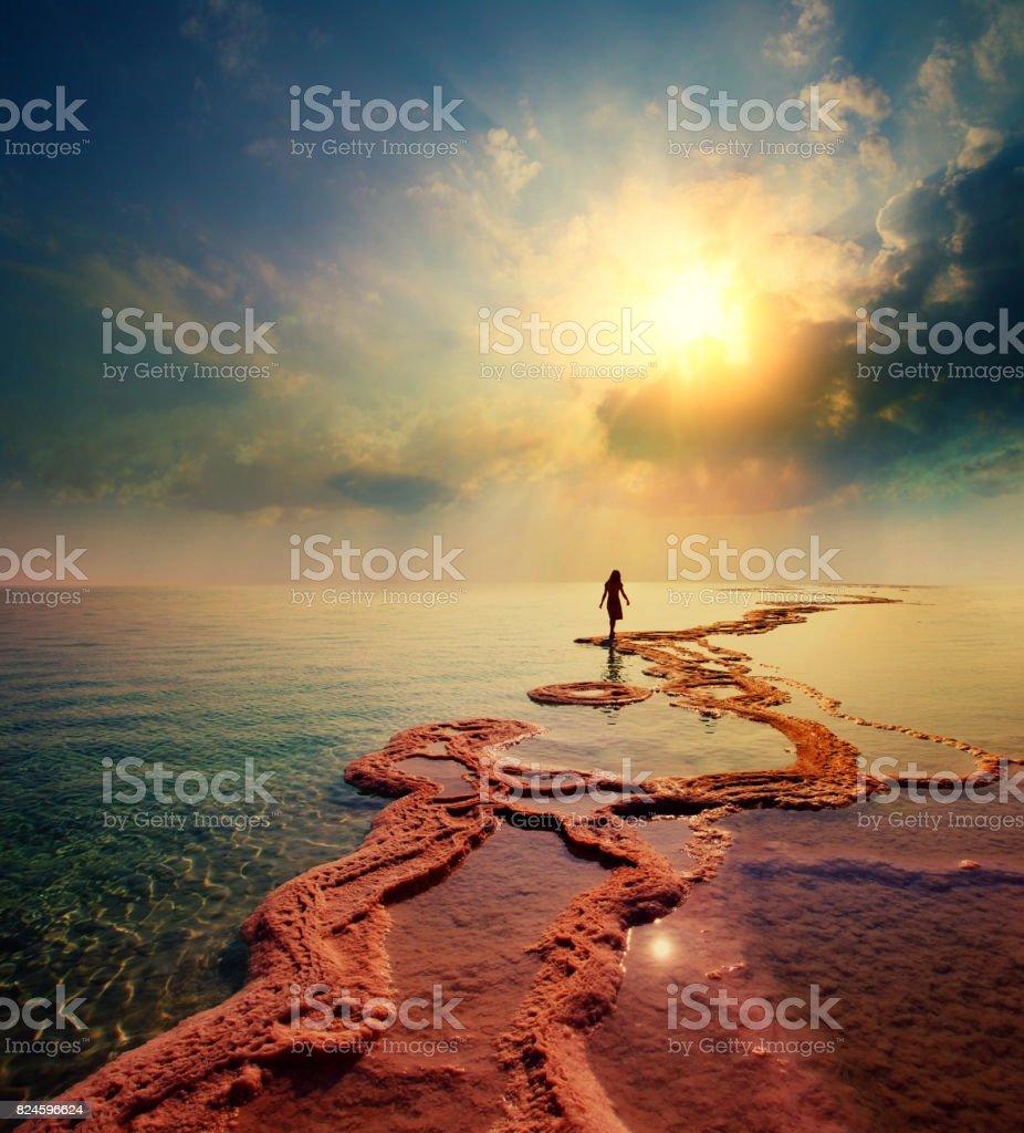 Frau zu Fuß direkt am Toten Meer Salz der Sonne entgegen – Foto