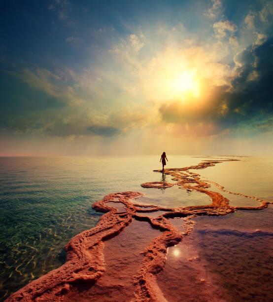 mulher andando na praia de sal do mar morto em direção ao sol - israel - fotografias e filmes do acervo
