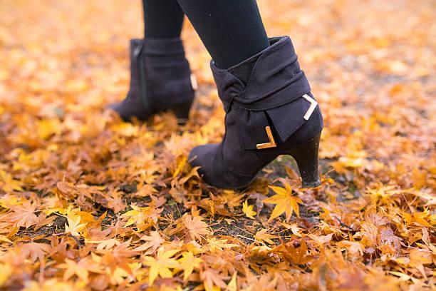 woman walking on fallen autumn leaves - damenschuhe k stock-fotos und bilder