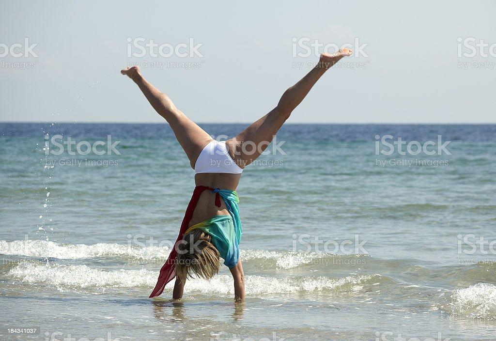 Woman walking on hands seaside stock photo