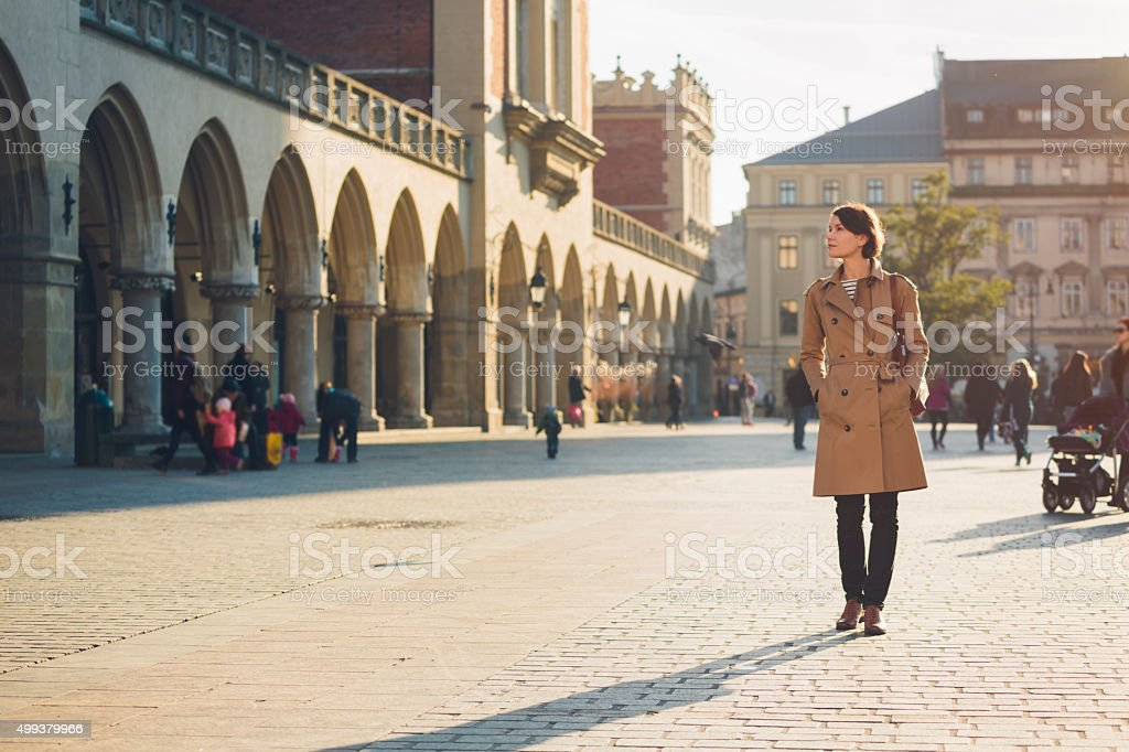 Woman walking on Main Market Square in Krakow. stock photo