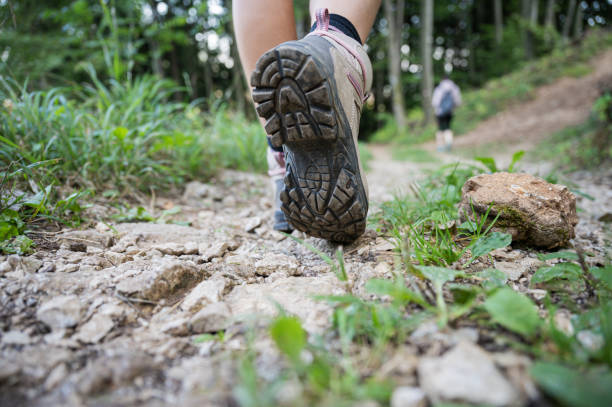 Woman walking on mountain trail stock photo