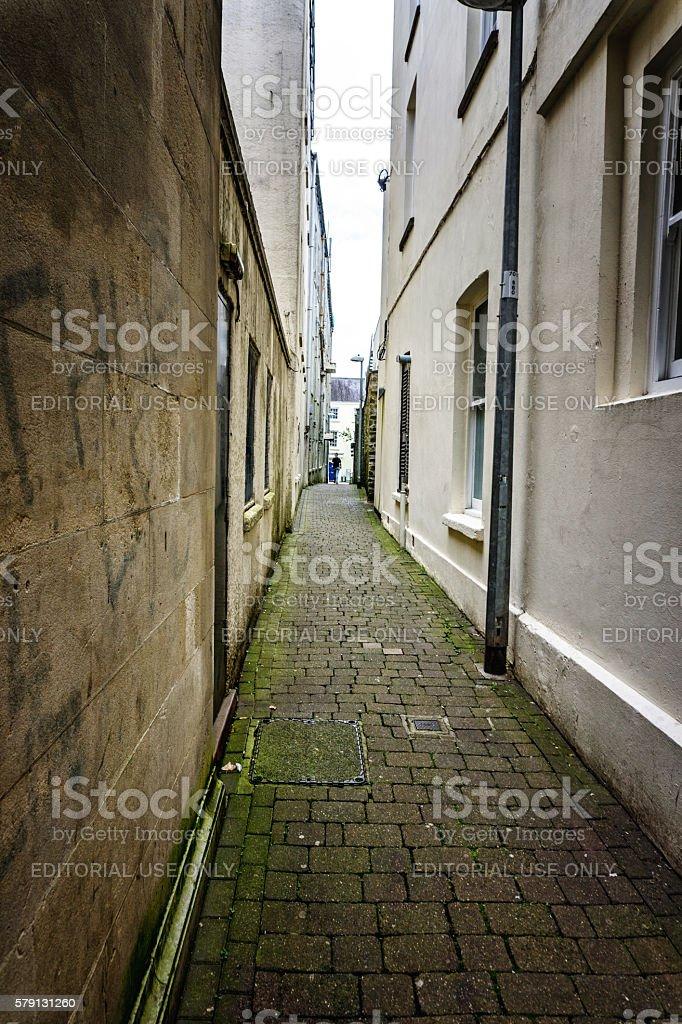 Woman walking on narrow alleyway stock photo