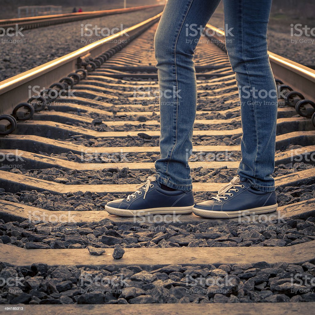 Woman walking on railroad. Female legs on the road stock photo