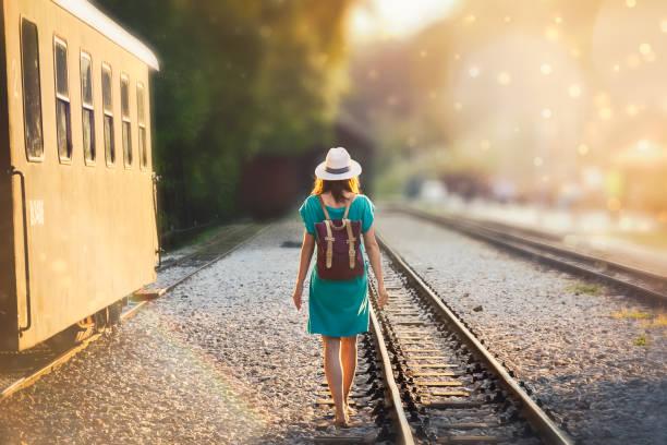 Woman walking on railway tracks in sunset stock photo