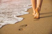 Beach travel - woman walking on sand beach leaving footprints in the sand. Closeup detail of female feet and golden sandBeach travel - woman walking on sand beach leaving footprints in the sand. Closeup detail of female feet and golden sand