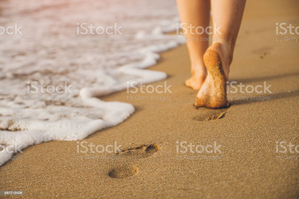 Woman walking on sand beach leaving footprints in the sand - Photo