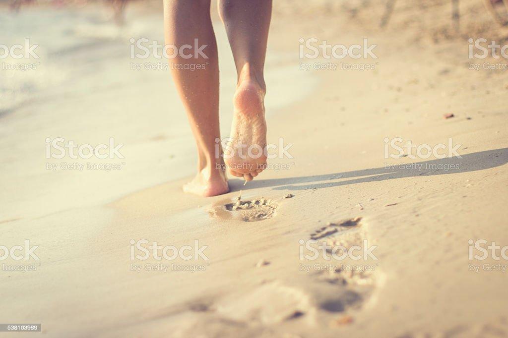 Woman walking on sand beach stock photo