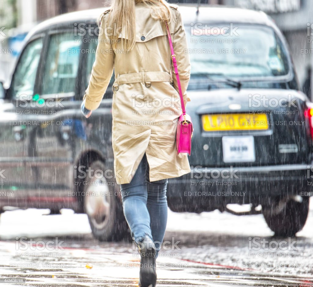 Woman walking on sidewalk against Taxi cab, rear view stock photo