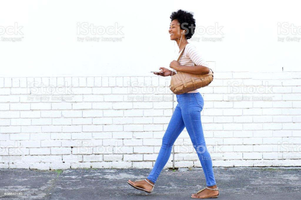 woman walking on sidewalk with headphones and smart phone - foto de stock