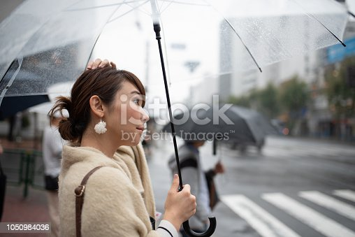 Woman walking in traditional old town of Kagurazaka, Tokyo, in a rainy day