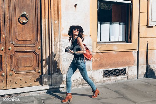 Side view of beautiful young woman walking on streets and taking pictures. Wears casual clothes, sunglasses, a hat and a backpack.