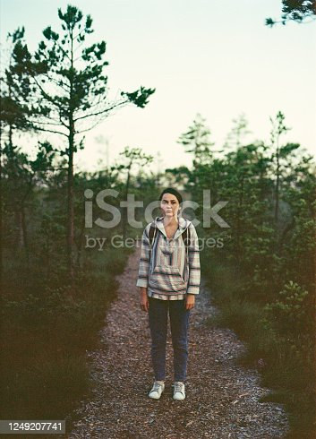 Young Caucasian woman with backpack  walking on swamp in the morning in Estonia