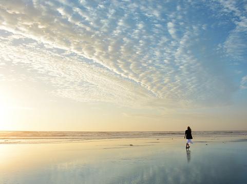 Woman Walking On The Beach At Sunrise Stock Photo ...