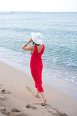 Woman in red dress wearing white hat walking on the summer beach.